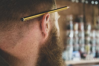 Close up of pencil over ear of bearded man with light brown hair.