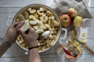 High angle close up of person placing apples in a round baking tin.