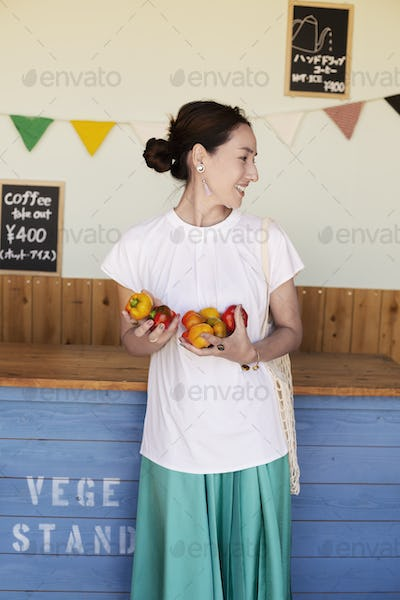 Smiling Japanese woman standing in a farm shop, holding vegetables.