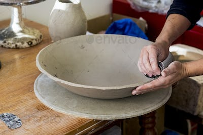 High angle close up of ceramic artist in her workshop, working on clay bowl.