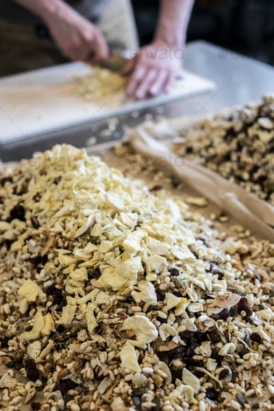 Close up of person standing in a kitchen, chopping food with chef's knife, heap of nuts, raisins and