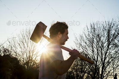 Bearded man walking outdoors at sunset, carrying large wooden mallet on his shoulder.
