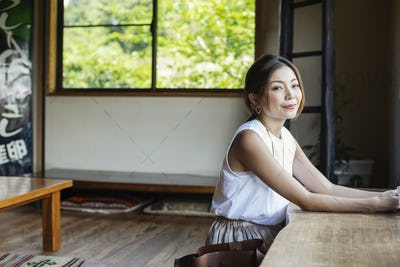 Smiling Japanese woman sitting at a table in a Japanese restaurant.