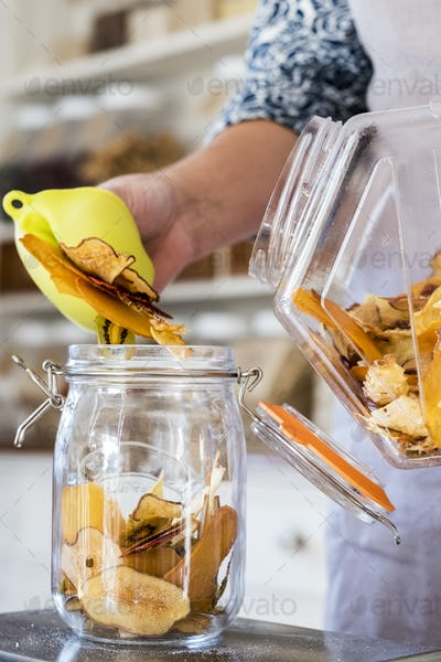 Close up of person standing in a kitchen, placing slices of dried fruit into glass jar.