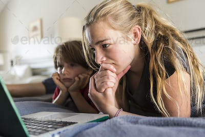 13 year old sister and her brother looking at laptop on bed