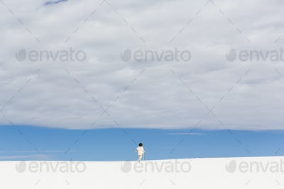 6 year old boy walking in white sand dunes, a strip of blue sky on the horizon and thick cloud.