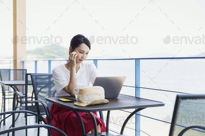 Female Japanese professional sitting on balcony of a co-working space, using laptop computer.