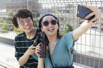 Young Japanese man and woman sitting on a rooftop in an urban setting, taking selfie with mobile