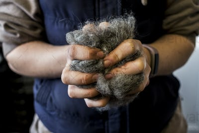 Close up of woman holding bunch of horse hair filling for saddle.