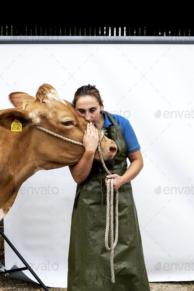 Portrait of female farmer wearing green apron with a Guernsey cow.