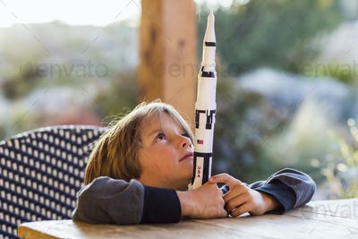 A boy playing with a toy Nasa Saturn 5 rocket, day dreaming about space flight.