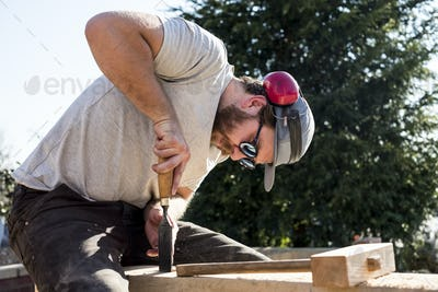 Man wearing baseball cap, sunglasses and ear protectors on building site, working on wooden beam.