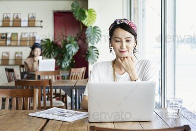 Female Japanese professional sitting at a table in a co-working space, using laptop computer.