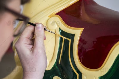 Close up of woman wearing glasses in a workshop, painting traditional wooden horse from