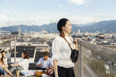 Smiling young Japanese woman standing on a rooftop in an urban setting.