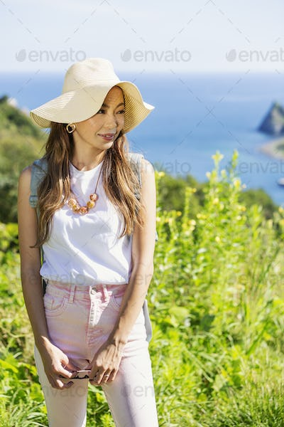 Japanese woman wearing hat standing on a cliff, ocean in the background.