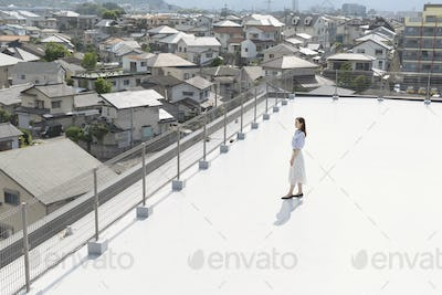 High angle view of Japanese woman standing on a rooftop in an urban setting.