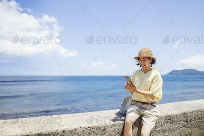 Japanese woman wearing hat sitting on a wall, ocean in the background.