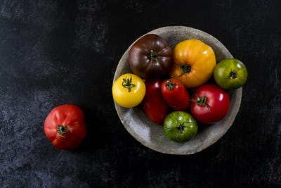 High angle close up of grey plate with selection of tomatoes in various shapes and colours on black
