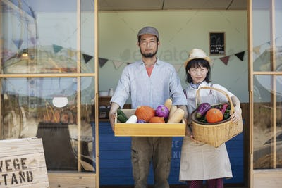 Japanese man and woman standing outside a farm shop, holding crate and basket with fresh vegetables,