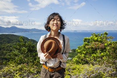 Japanese woman holding hat standing on a cliff, ocean in the background.