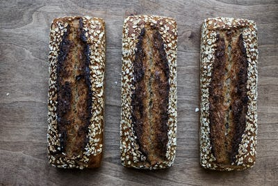High angle close up of three freshly baked seeded loaves of bread in an artisan bakery.