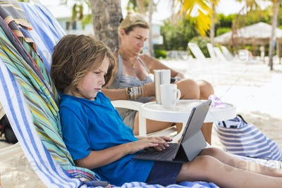 5 year old boy using laptop at the beach