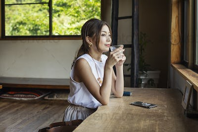 Smiling Japanese woman sitting at a table in a Japanese restaurant, drinking.