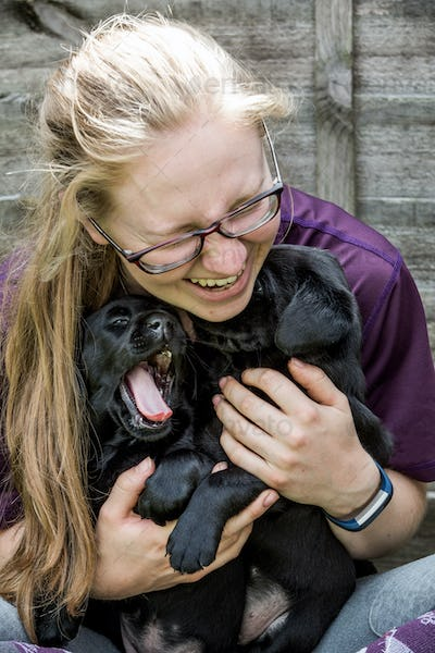 Blond woman wearing glasses hugging two Black Labrador puppies.
