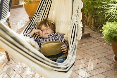 portrait of 6 year old boy lying in hammock on porch