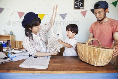 Japanese man, woman and boy standing in a farm shop, sorting clear plastic bottles into basket.