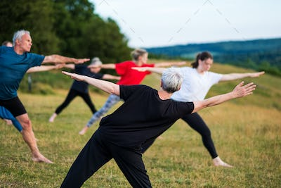 Group of women taking part in a yoga class on a hillside.