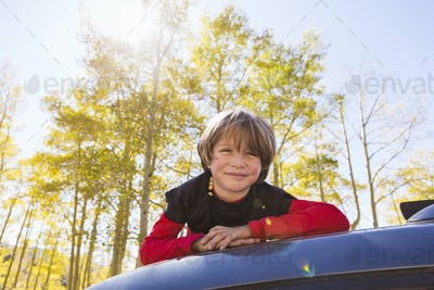 A smiling 6 year old boy lying on the hood of a blue SUV in woodland.
