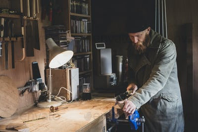 Bearded man wearing black beanie standing at workbench in workshop, sawing piece of wood.