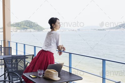Female Japanese professional standing on balcony of a co-working space, laptop computer on table.