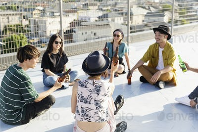 Smiling group of young Japanese men and women sitting on a rooftop in an urban setting.