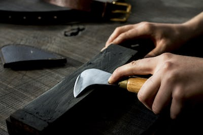 High angle close up of person sharpening saddle making tool on whetstone.