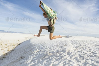 Athletic 13 year old girl leaping in the sand, White Sands Nat'l Monument, NM