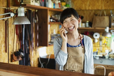 Smiling Japanese woman wearing apron standing in a leather shop, talking on her mobile phone.