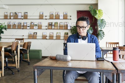 Male Japanese professional sitting at a table in a co-working space, using laptop computer.