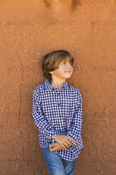 portrait of 6 year old boy against adobe wall