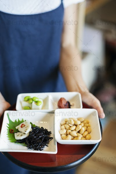 High angle close up of waitress holding a selection of vegetarian Japanese foods in a cafe.
