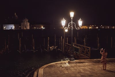 Woman taking picture of a streetlight by a lagoon in Venice, Veneto, Italy, at night.