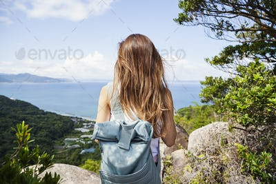 Rear view of woman carrying backpack standing on a rock on cliff, ocean in the background.