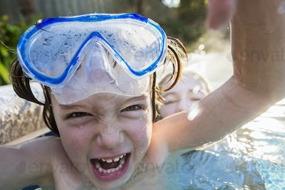 A boy in goggles laughing at the camera, in a warm swimming pool with his sister.