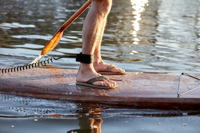 Close up of legs of man standing on paddleboard on river