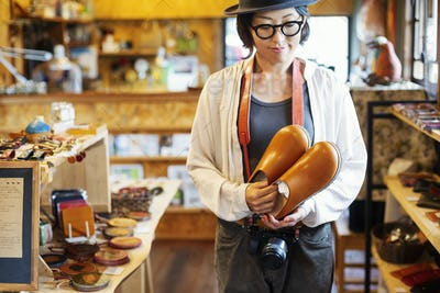 Japanese woman wearing hat and glasses standing in a leather shop, holding pair of leather shoes.