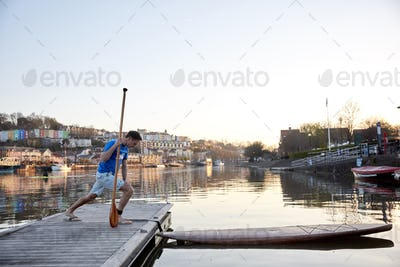 Man holidng paddle stretching legs on riverside jetty before using paddleboard