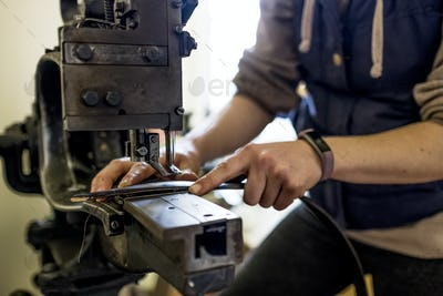 Female saddler standing in workshop, sewing leather strap on saddlery sewing machine.