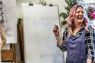 Laughing woman wearing apron standing at an easel, drawing of human hand.